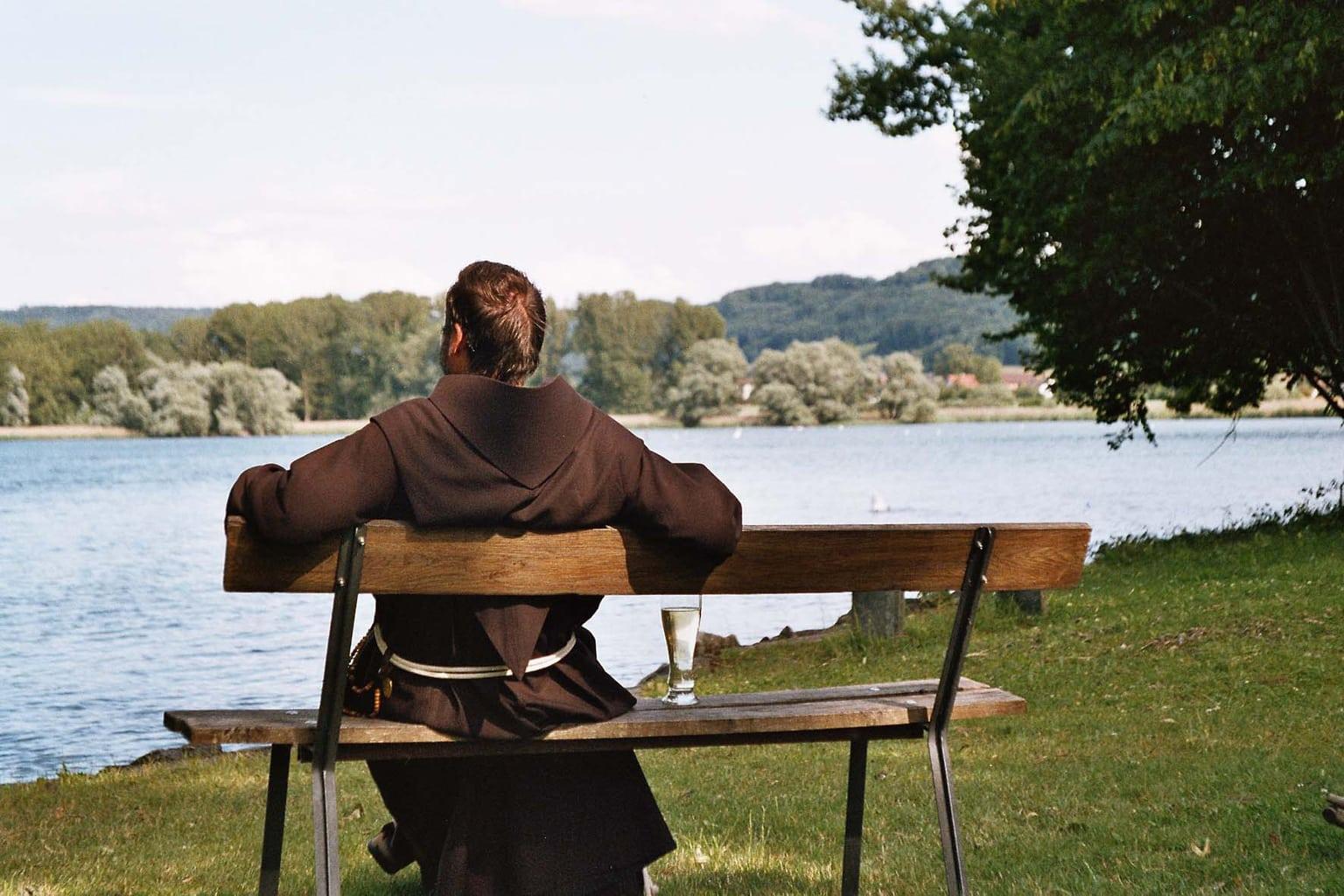 Een monnik met een glas water kijkt dromerig op de Bodensee
