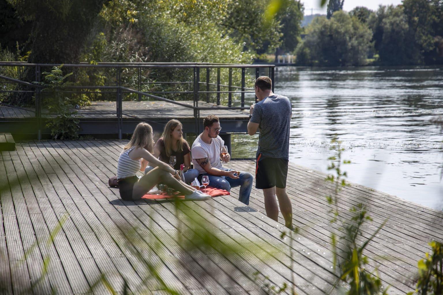 Jonge mensen tijdens een picknick aan de oevers van de Main, ook dat hoort bij wellness in Franken