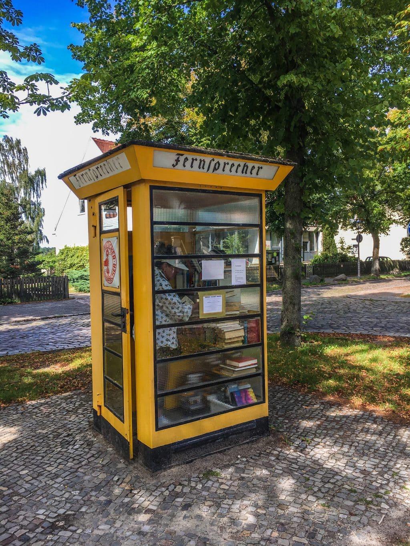 Een ouderwetse gele telefooncel in de Berlijnse wijk Alt-Lübars