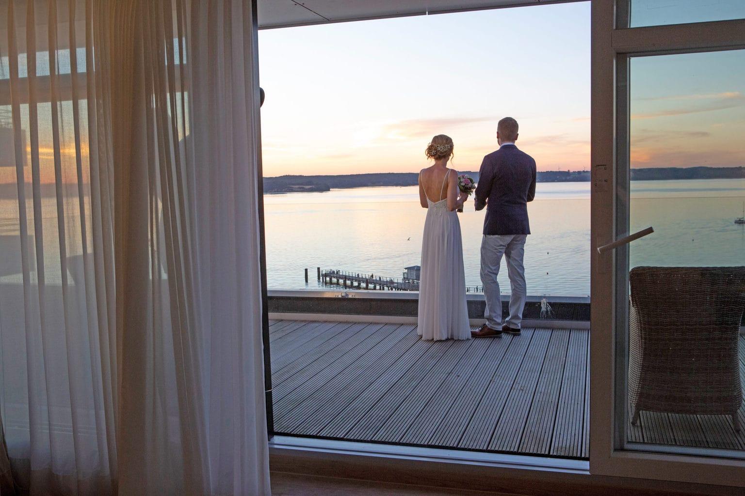 Verliefd stel op het terras bebijkt zonsondergang aan de Oostzee