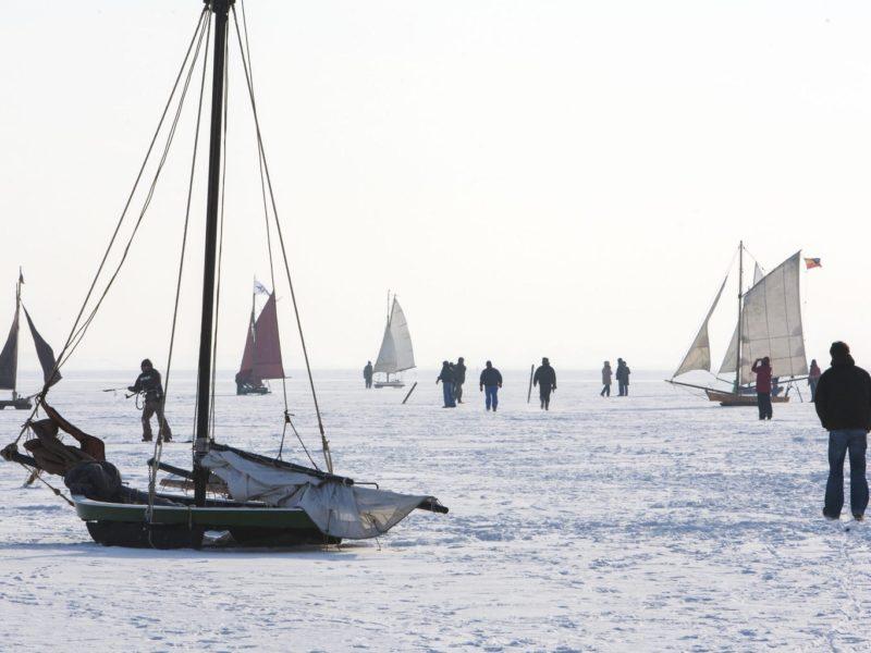 Ijszeilers en voetgangers op de bevroren Bodden in Fischland-Darß-Zingst