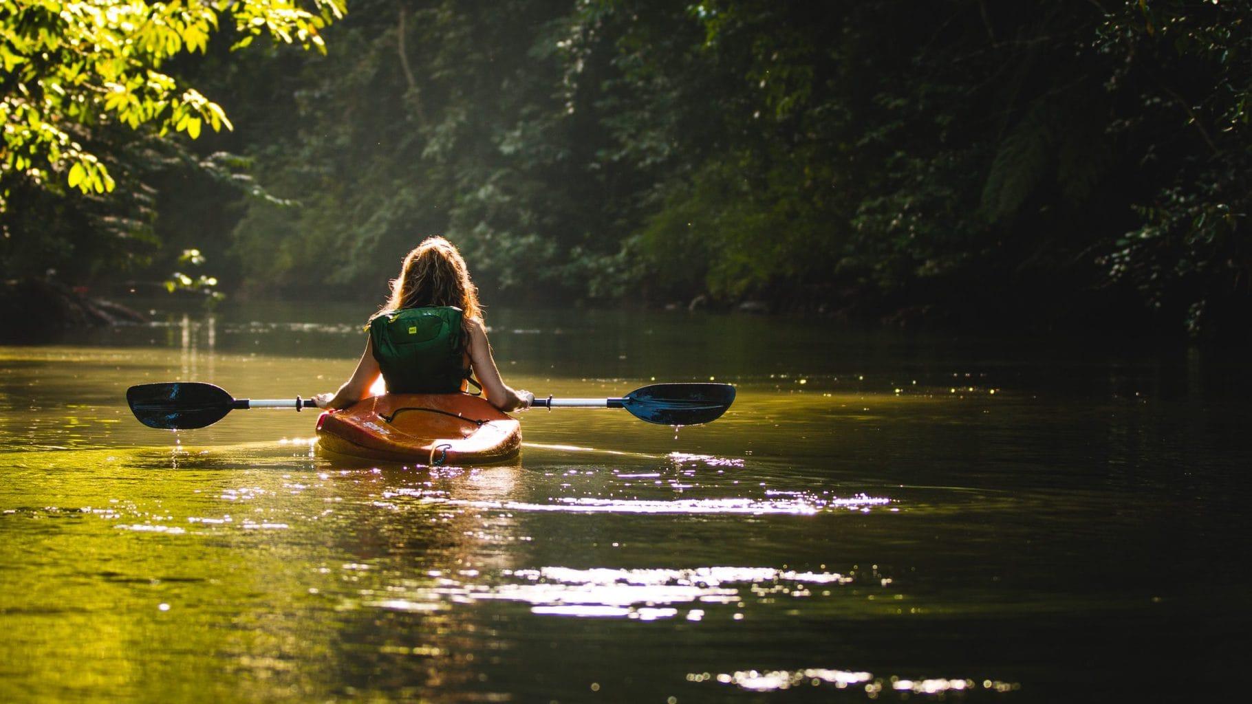 Een jonge vrouw vermaakt zich in een kano in het Beierse Woud