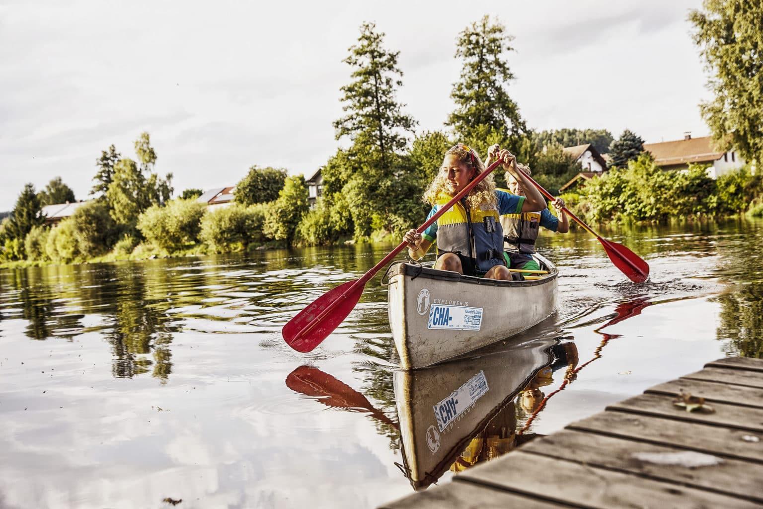 Een vrouw en een man samen in een kano op een meertje in het Beierse Woud in Duitsland