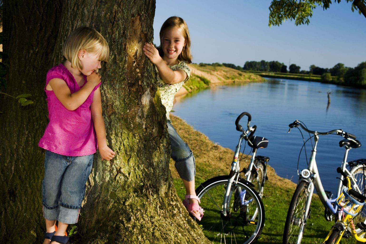 Kinderen spelen met bomen en fietsen met zicht op het water in het Duitse Emsland
