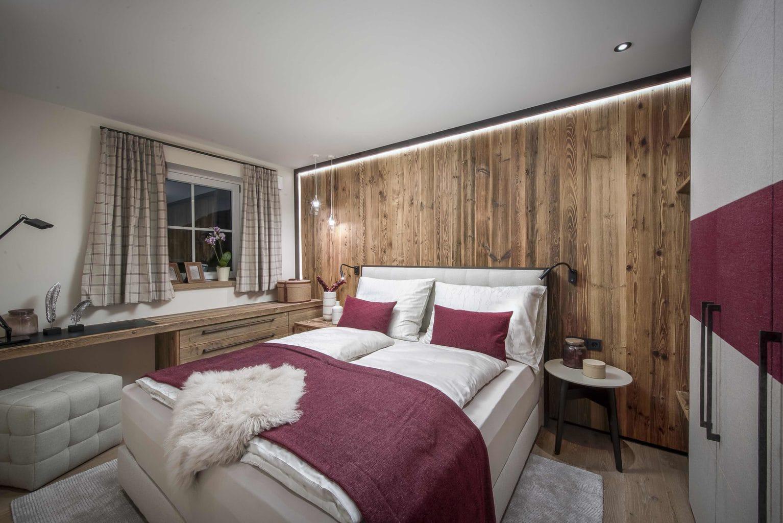 Slaapkamer met boxspringbed en veel warm hout in vakantiepark R6 aan de Tegernsee