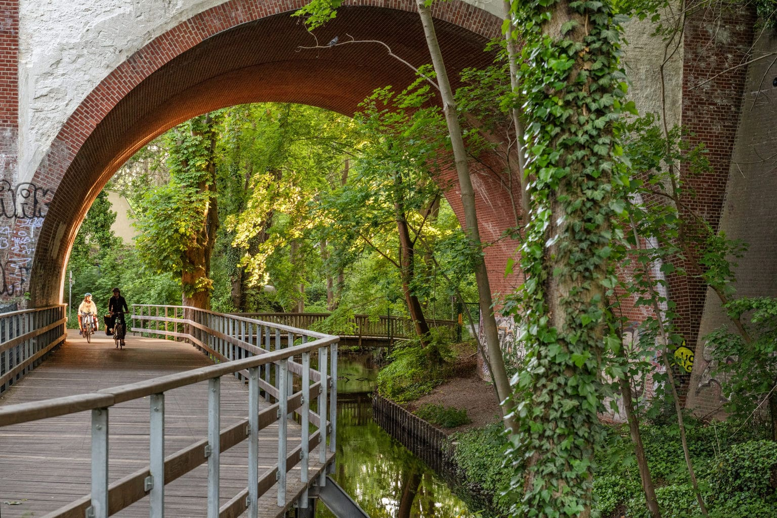 Een fietspad onder een brug in een bos met de Tegeler Fließ, en beekje in de Berlijnse wijk Reinickendorf
