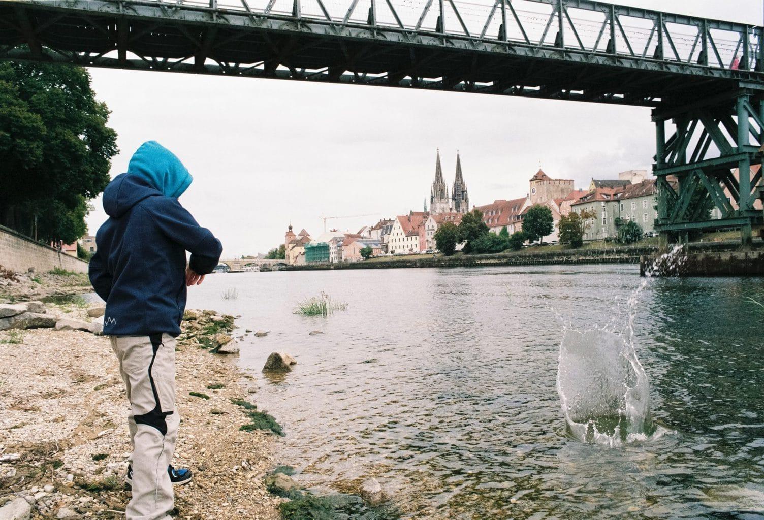 Jonge gooit steentjes aan de Donau in Regensburg