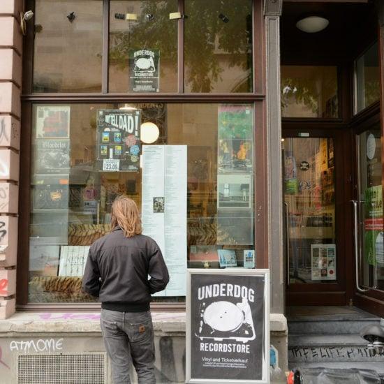 Een jonge man voor de etalage van Underdog Records in Keulen