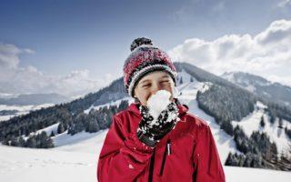 Een kind met een sneeuwbal in de Allgäuer Hörnerdörfer