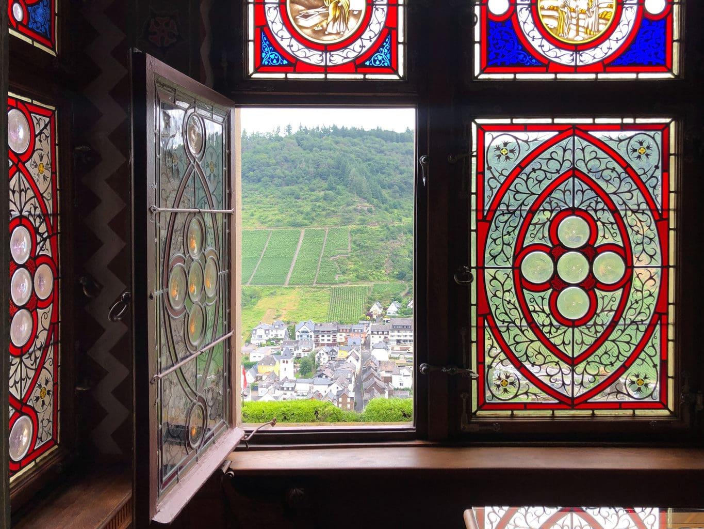 Open raam van Rijksburcht Coburg met een wijnberg op de achtergrond