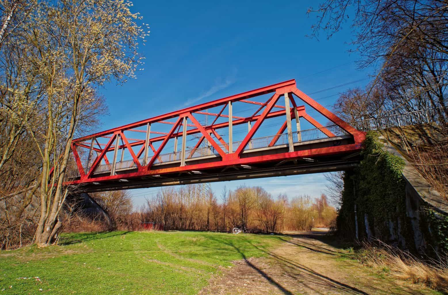 Een rode brug in het Roergebied met een fiets op de achtergrond