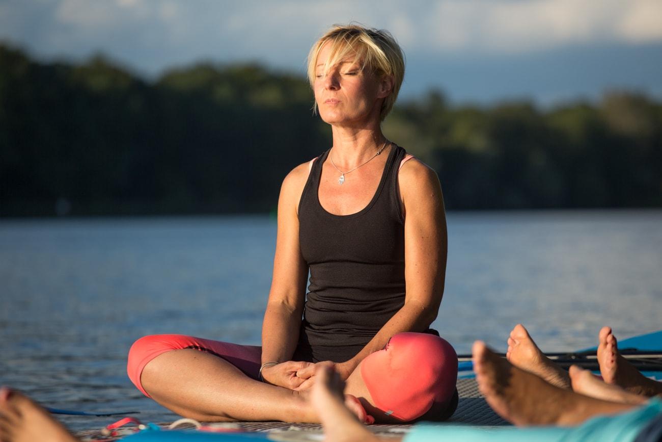 Lerares Angelique volledig ontspand op haar SUP-board tijdens het SUP-yoga