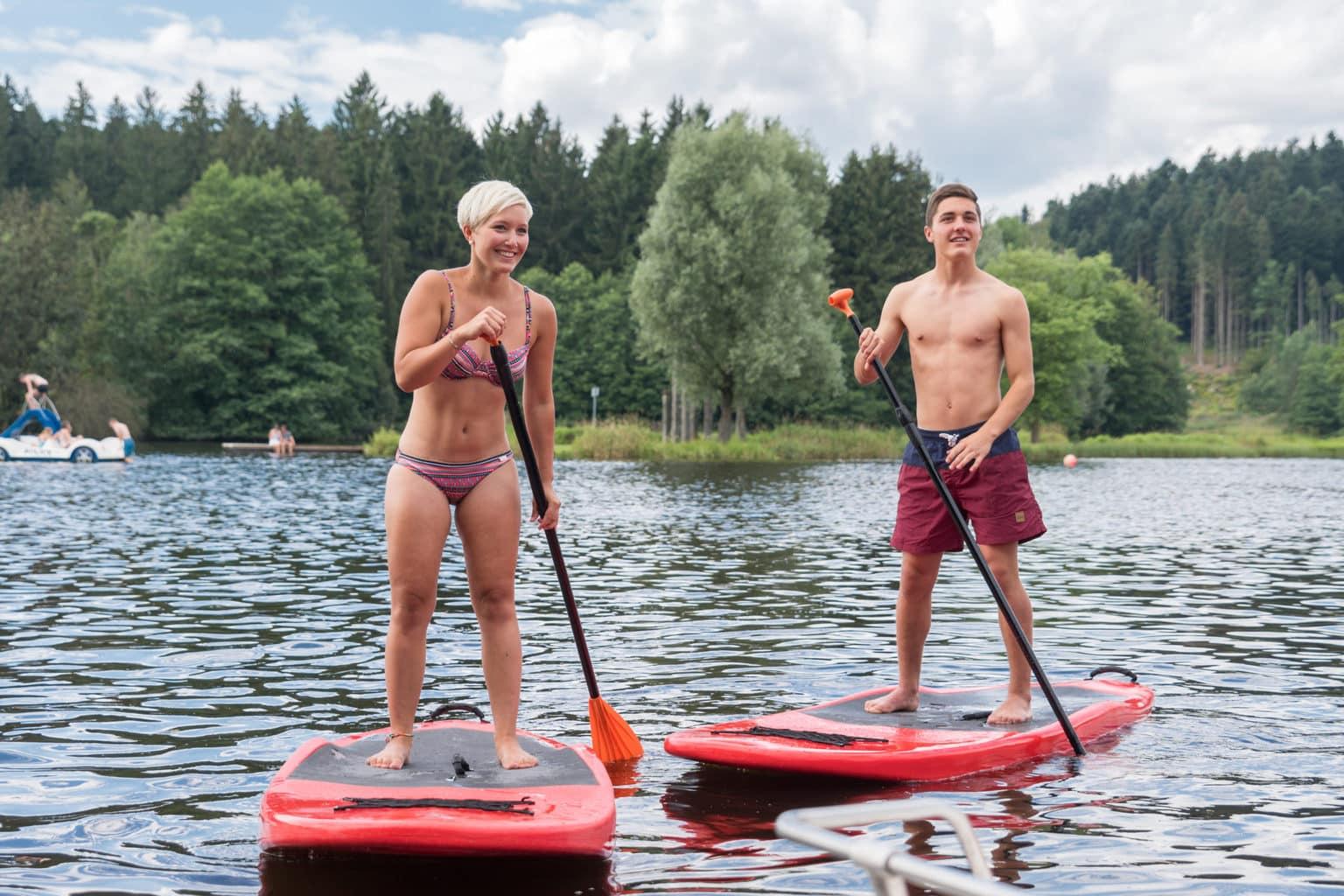 Een jonge vrouw en een jonge man SUPpen op de Rannasee in het Beierse Woud