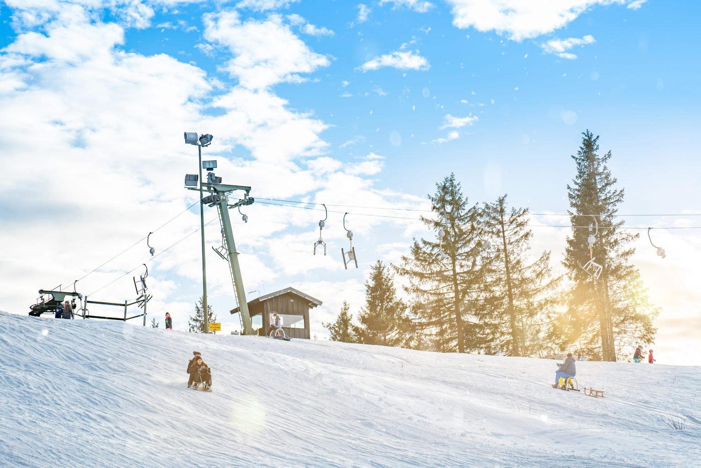 Kinderen op een slee op een piste in het Duitse skigebied Winterberg