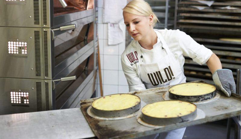 Een jonge vrouw schuift handgemaakte taarten in de oven bij Café Wild in het Bergische Land