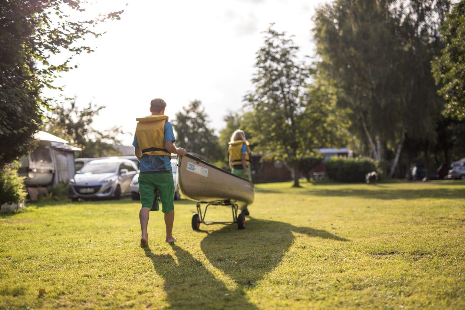 Twee sportes rollen hun kano weg op weg naat een tour bij de Regen in het Beierse Woud