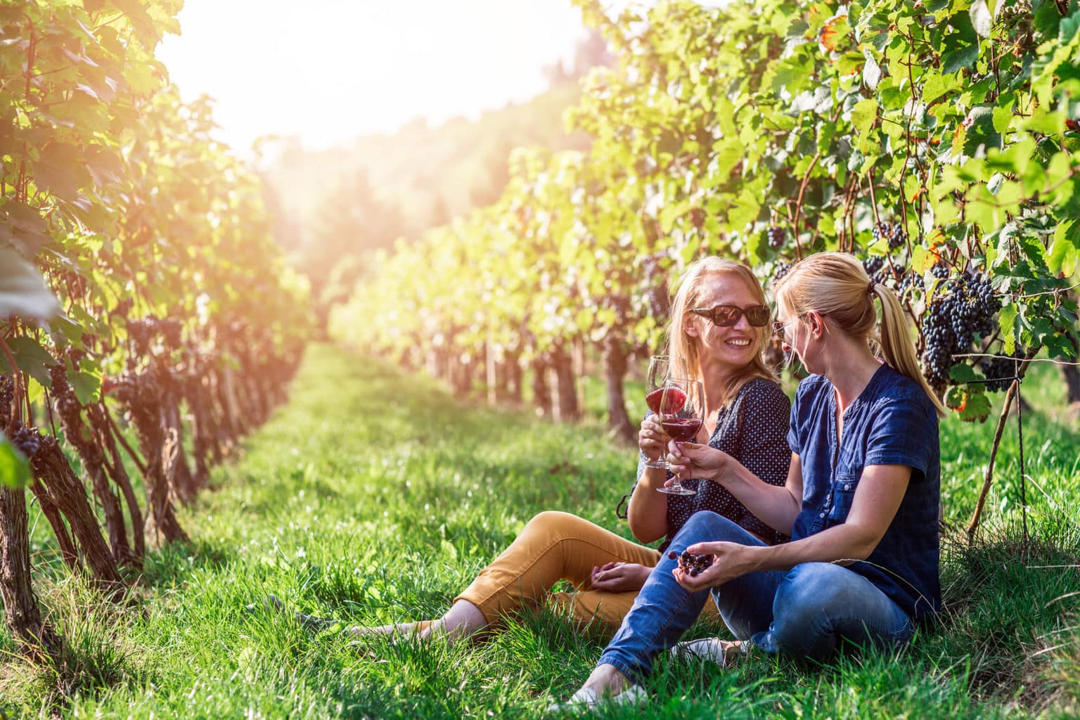 Twee vrouwen drinken wijn tussen de wijnstokken in de regio Saale-Unstrut in het oosten van Duitsland