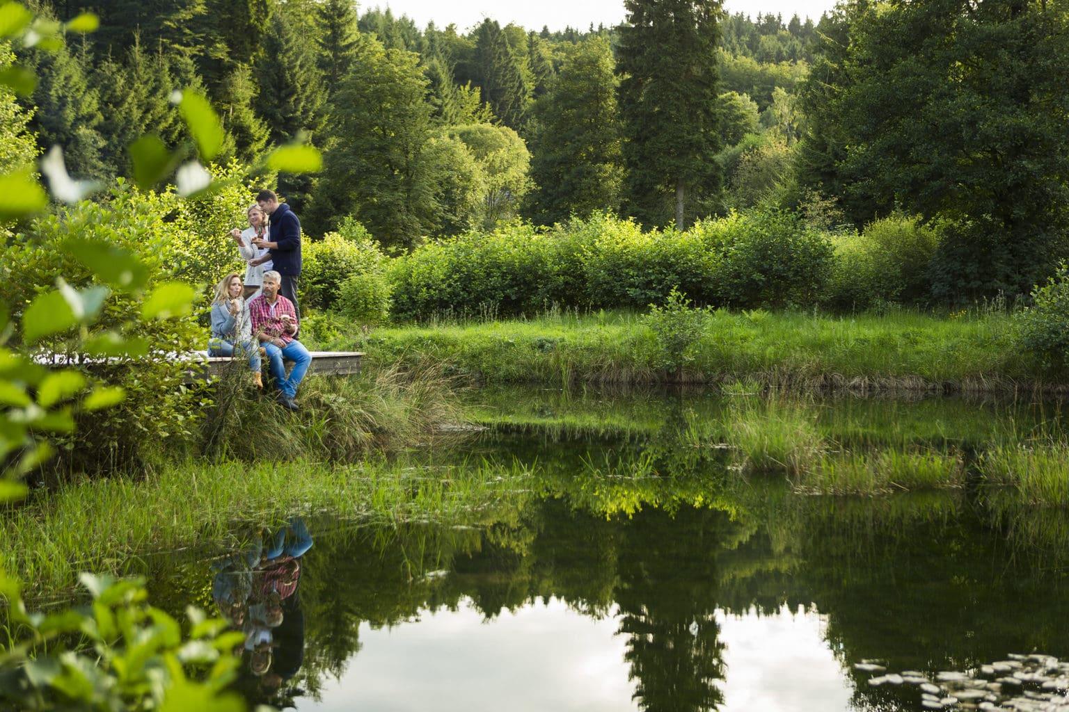 Wandelaars aan een meertje in Thüringen op zoek naar geneeskundige kruiden