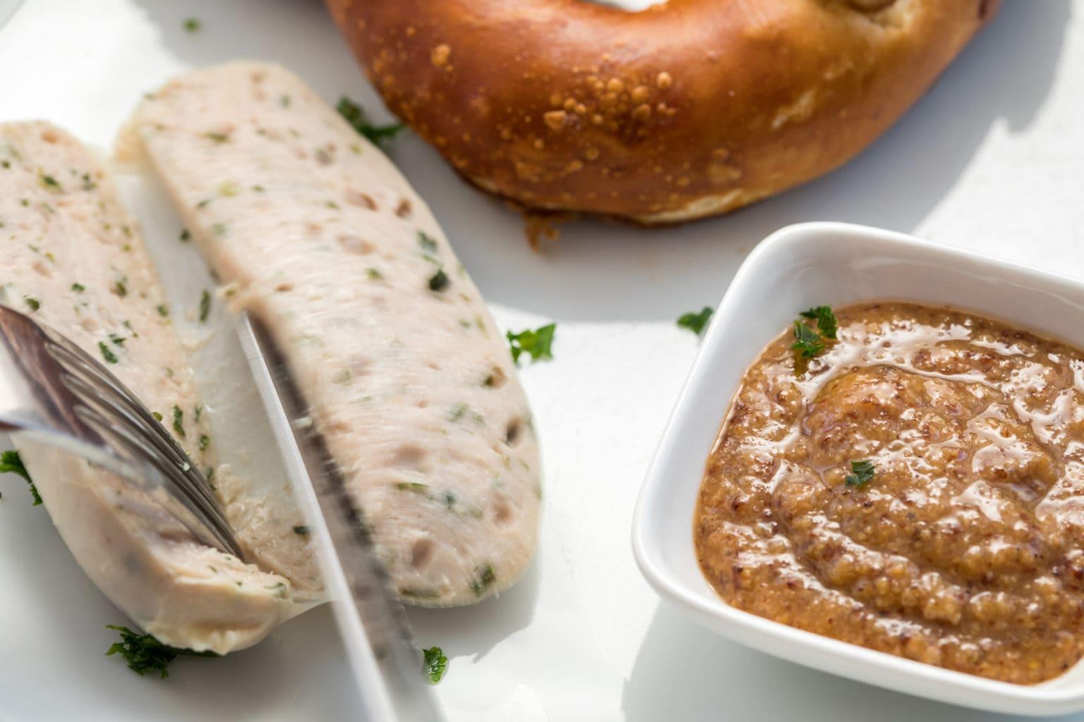 Opengesneden Weißwurst op de huid met mosterd en Brezel