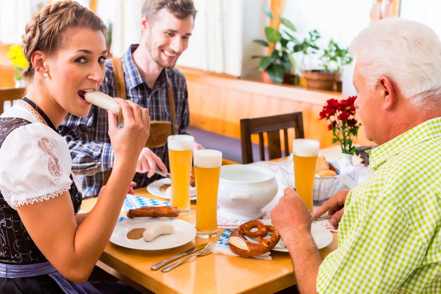 Drie mensen in volksdracht genieten van Weißwurst, Weizenbier, Brezel en mosterd