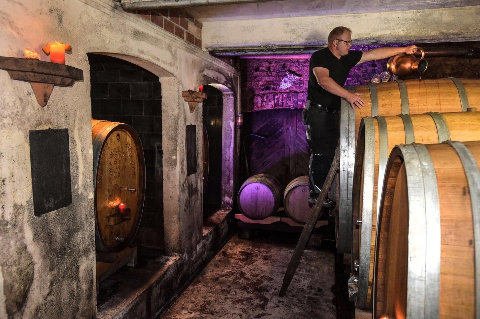 Wijnmaker kijkt bovenop eijnvaten bij Weingut Maier in Baden-Württemberg