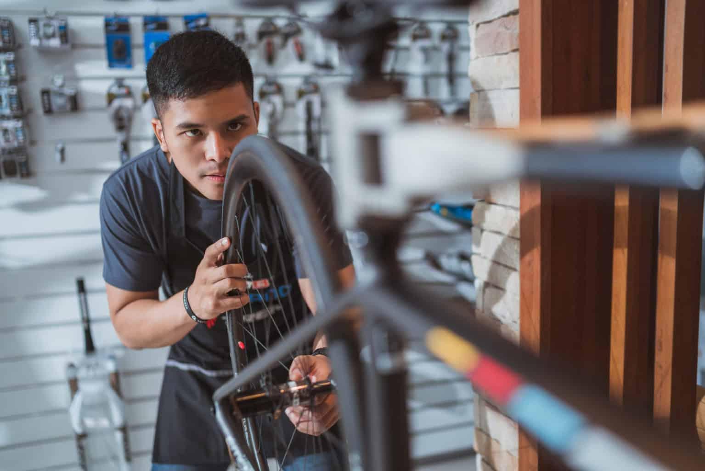 Een jonge man repareert een fiets