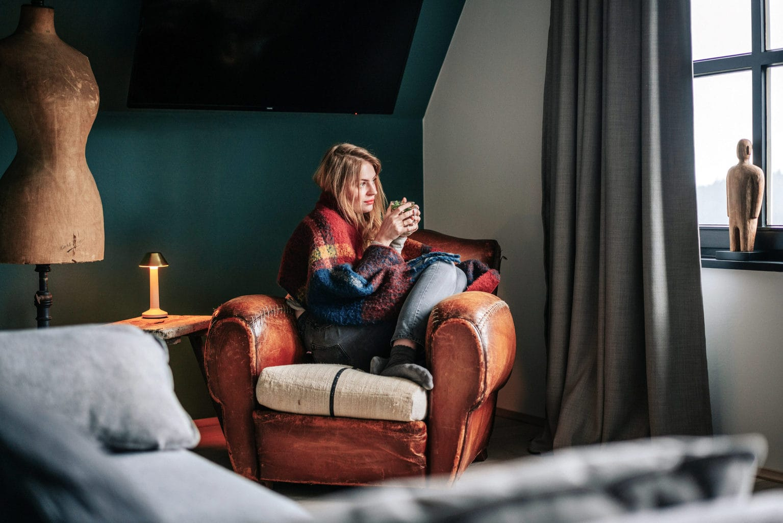 Een vrouw drinkt een kopje thee in een fauteuil in Hearts Hotel