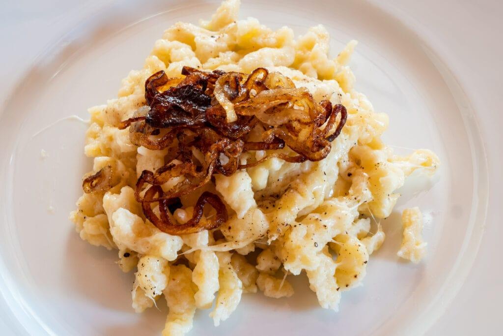 Duitse Käsespätzle met gebraden uien op een bord behoren tot de lievelingsgerechten van toeristen in Duitsland