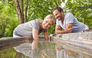 Man en vrouw nemen een armbad in koud water in Bad Wörishofen in Beieren