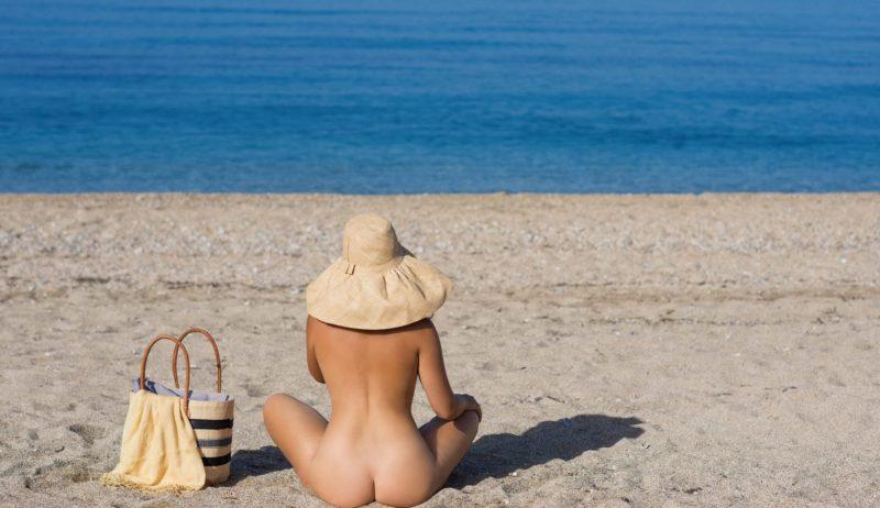 Een naakte vrouw met hoed zit op een strand in Duitsland