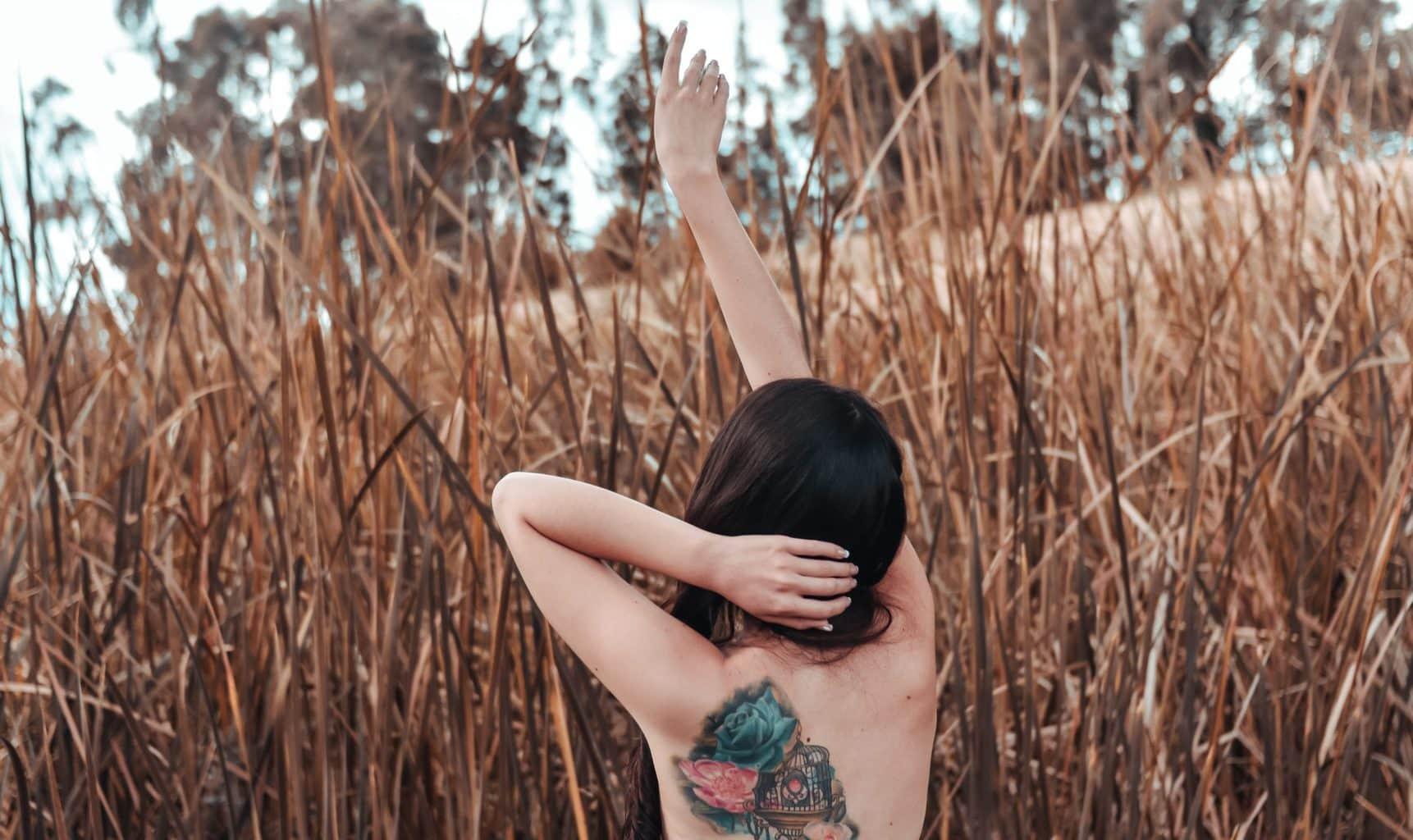 Getatoeeerde vrouw voor een veld