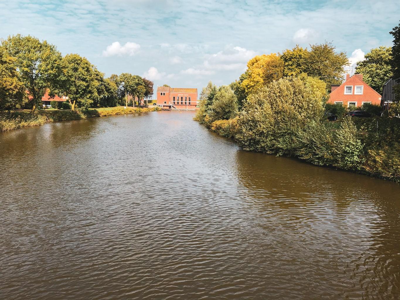 Een riviertje in Oost-Friesland met baksttenhuizen