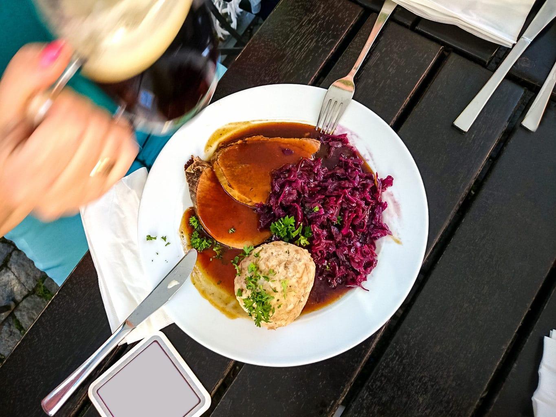 Een bord met Sauerbraten, knoedels en rode kool