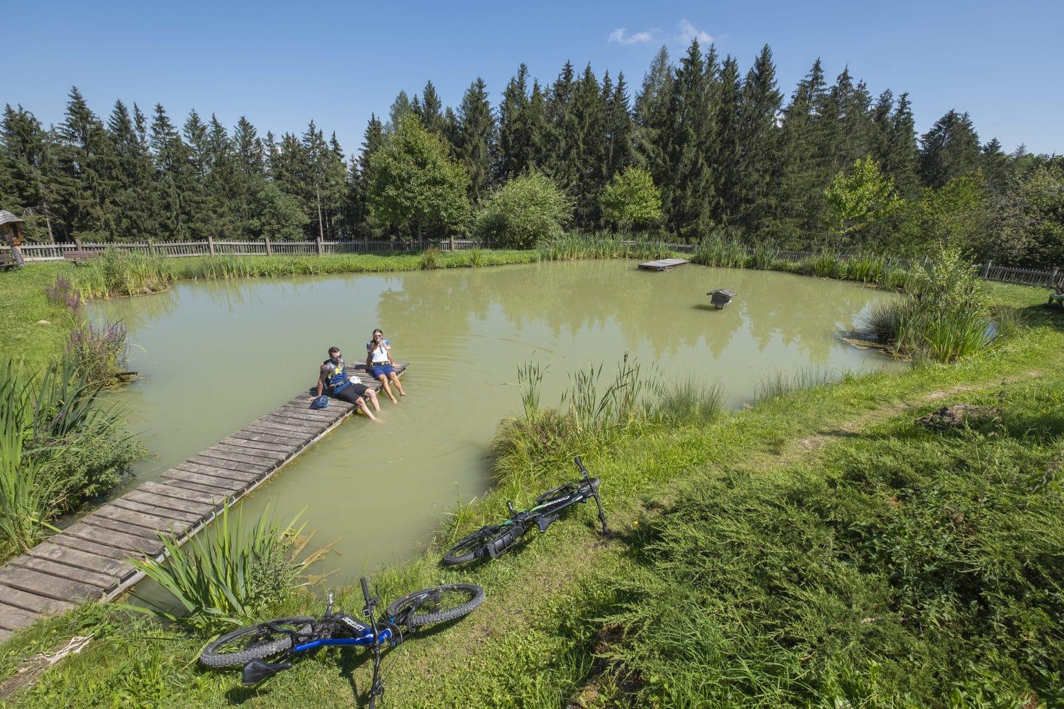 Met de voeten in het water genieten mountainbikers van een pauze aan een meertje in de Chiemgau