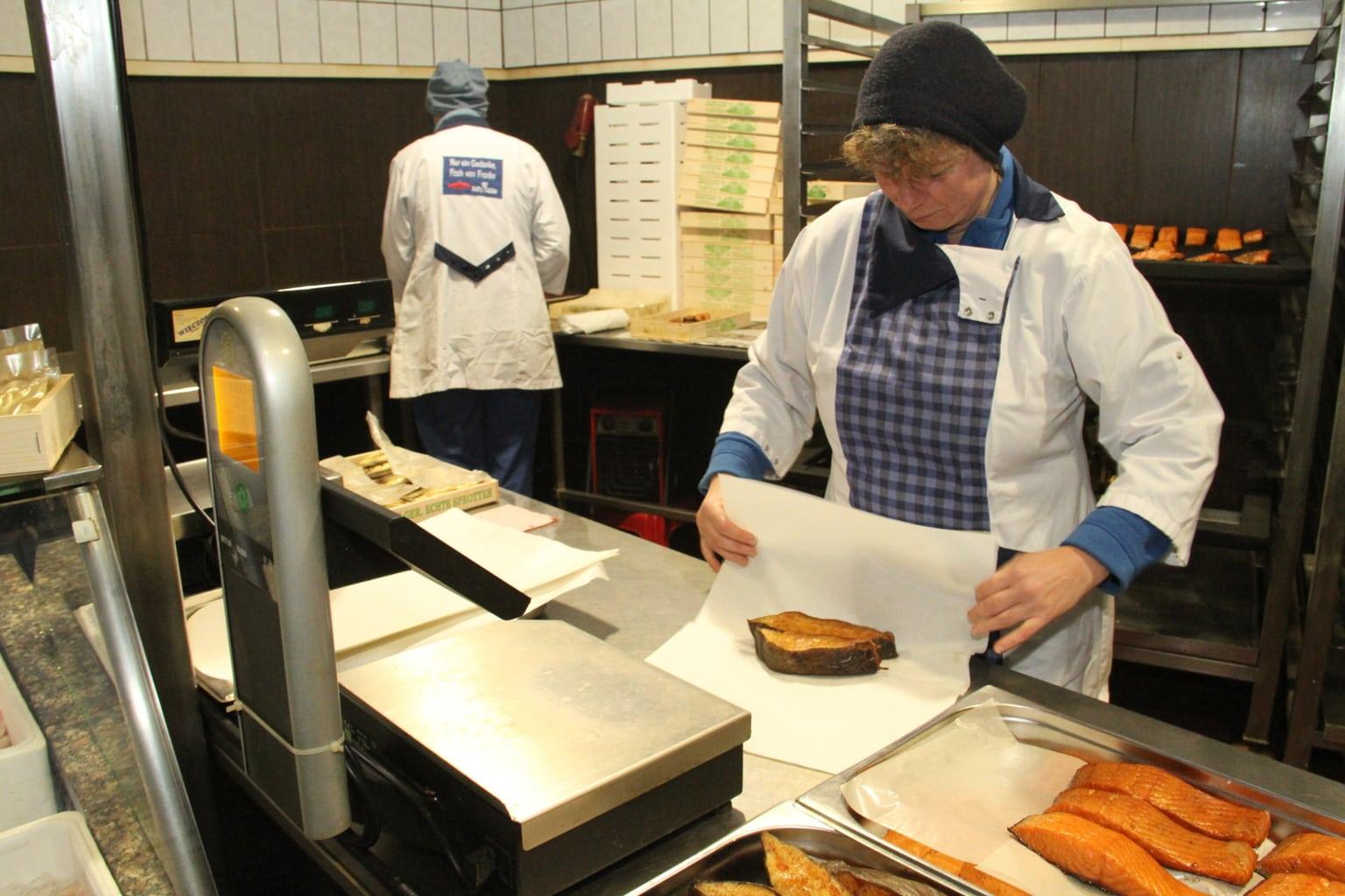 Een vrouw verpakt gerookte vis in een rokerij in Bremerhaven