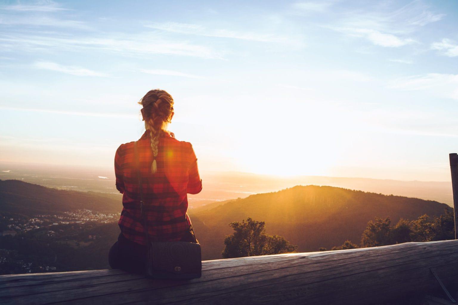 Een vrouw kijkt na een Urban Hike vanaf een berg op de zonsondergang