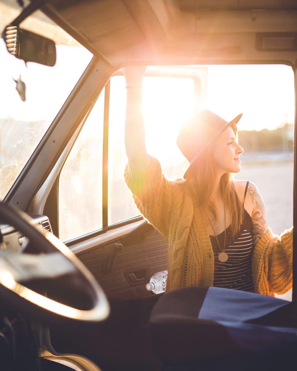 vrouw stapt in het tegenlicht in een campervan