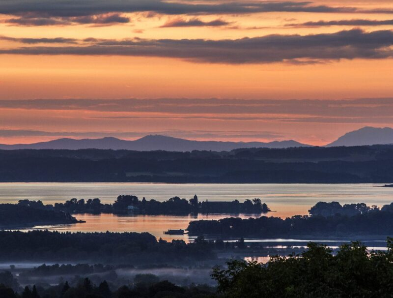 Uitzicht op de Chiemsee, de eilanden en de bergen tijdens zonsondergang