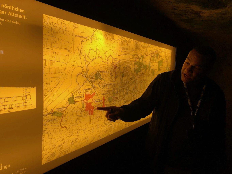 Stadgids Richard Selke laat op de plattegrond zien waar kelders en rotsgangen zijn in Neurenberg